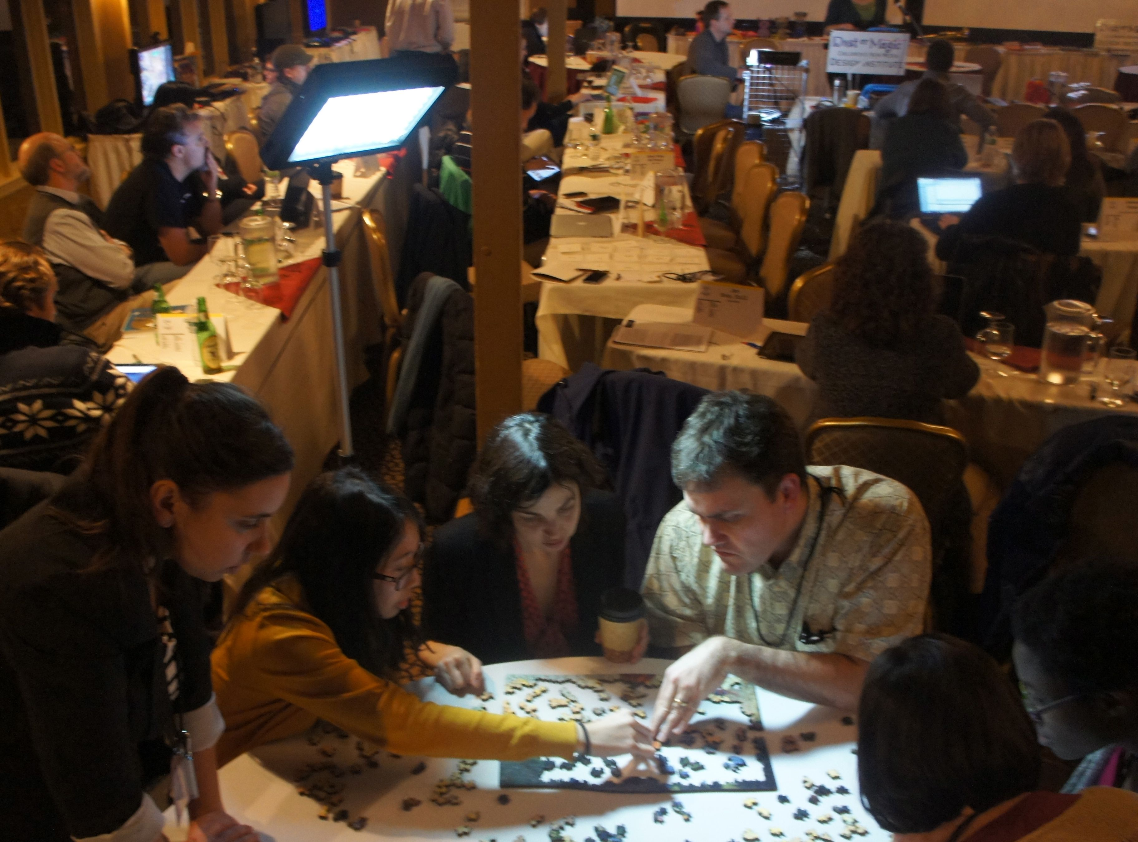 Jesse Schell leads a team on a very low tech jigsaw puzzle, as he listens to a demo in progress on Monday night.